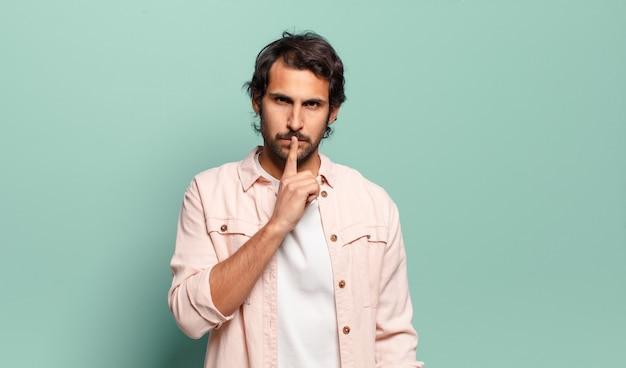 Молодой красивый индийский мужчина выглядит серьезным и крестным с пальцем, прижатым к губам, требуя тишины или тишины, сохраняя секрет