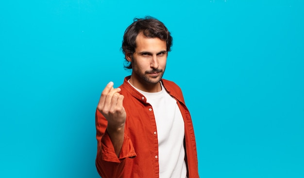 Young handsome indian man making capice or money gesture, telling you to pay your debts!
