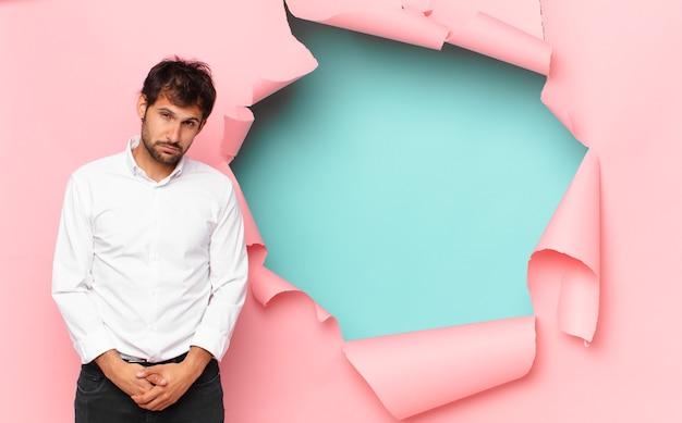 Молодой красивый индийский мужчина с грустным выражением лица против сломанной бумажной дыры