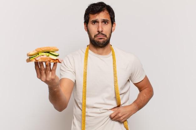 젊은 잘 생긴 인도 남자 슬픈 표정과 샌드위치를 들고