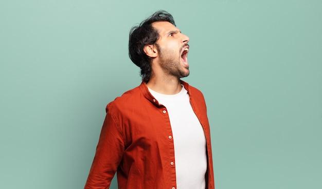 猛烈に叫び、積極的に叫び、ストレスと怒りを見て若いハンサムなインド人