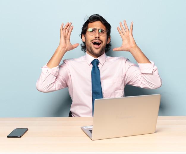 怒り、欲求不満、ストレス、動揺を感じて、空中で手を上げて叫んでいる若いハンサムなインド人。ビジネスとフレランサーの概念