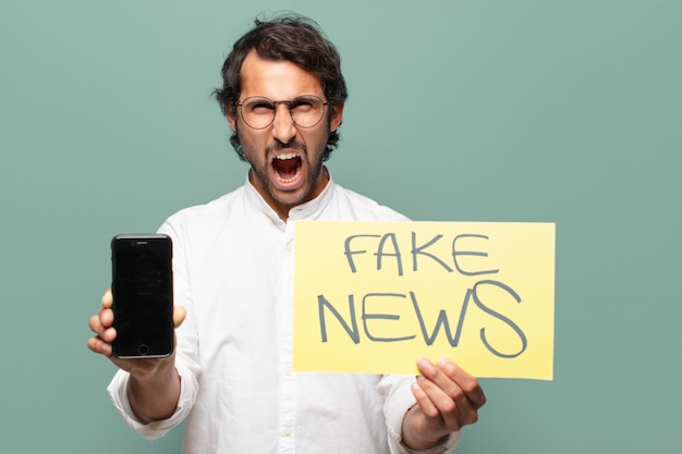 彼のセル画面を表示している若いハンサムなインド人。フェイクニュースのコンセプト