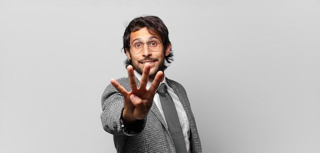 Молодой красивый индийский мужчина улыбается и выглядит дружелюбно, показывает номер четыре или четвертый с рукой вперед, отсчитывая. бизнес-концепция