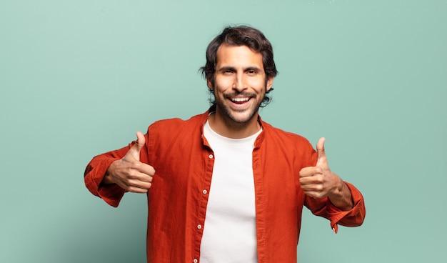 두 엄지 손가락으로 광범위하게 행복, 긍정적, 자신감과 성공을 찾고 웃고있는 젊은 잘 생긴 인도 남자