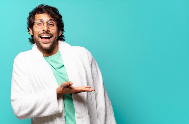 陽気な笑顔、幸せを感じ、手のひらとバスローブを着てコピースペースでコンセプトを示す若いハンサムなインド人