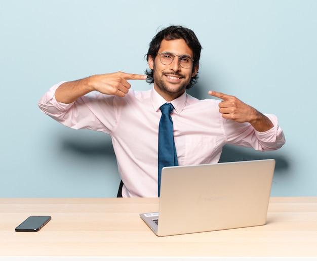 自信を持って笑顔の若いハンサムなインド人男性は、自分の広い笑顔、前向きで、リラックスした、満足のいく態度を指しています。ビジネスとフレランサーの概念