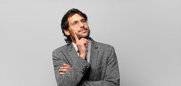 행복 하 게 웃 고 공상 또는 의심, 측면을 찾고 젊은 잘 생긴 인도 남자. 비즈니스 개념