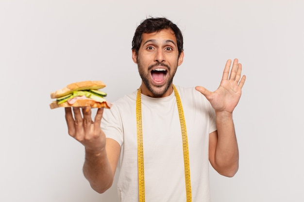 Молодой красивый индийский мужчина удивлен выражением лица и держит бутерброд