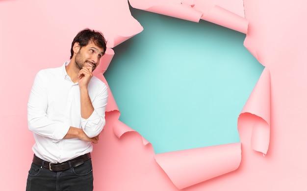 壊れた紙の穴に対して表現を考えている若いハンサムなインド人