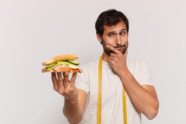 表現を考え、サンドイッチを保持している若いハンサムなインド人