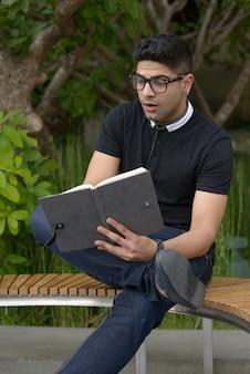 本を読んで、公園でショックを受けた眼鏡をかけた若いハンサムなインド人