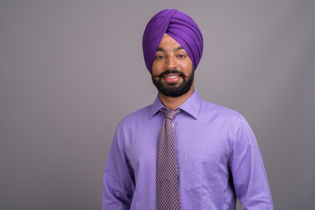 灰色のターバンを身に着けている若いハンサムなインドのシーク教徒のビジネスマン