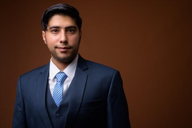 Молодой красивый иранский бизнесмен против коричневой стены