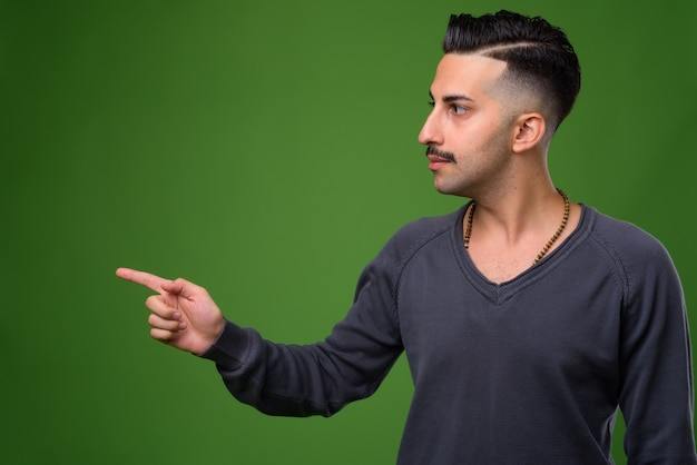 Young handsome iranian man with mustache on green