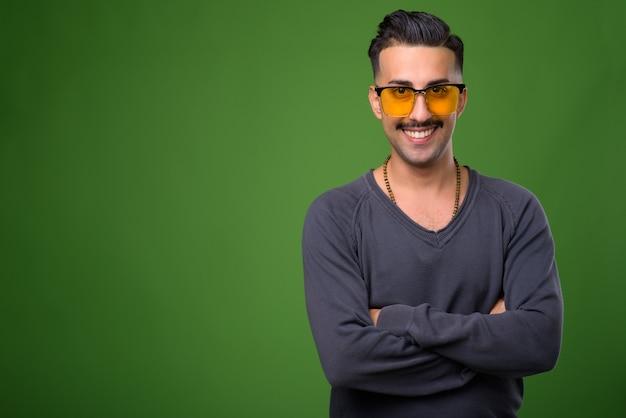 Молодой красивый иранский мужчина с усами на зеленом