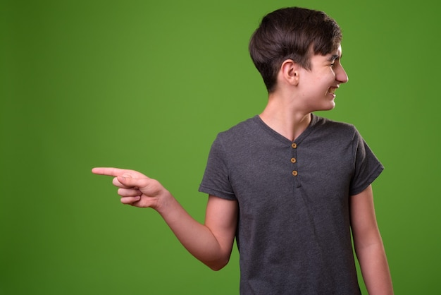 Young handsome iranian teenage boy pointing finger