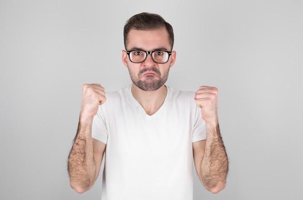 Молодой красивый латинский мужчина в повседневной футболке, стоящий у изолированной белой стены, злой и безумный, поднимает кулаки разочарованно и в ярости, кричит от гнева. ярость и агрессивная концепция.