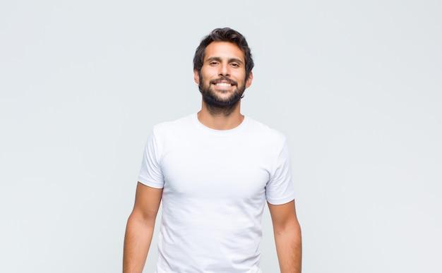 Молодой красивый латинский мужчина позирует и смотрит в камеру у белой стены