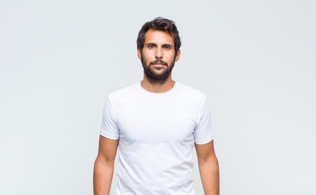 ポーズをとって白い壁に正面を向いている若いハンサムなラテン男