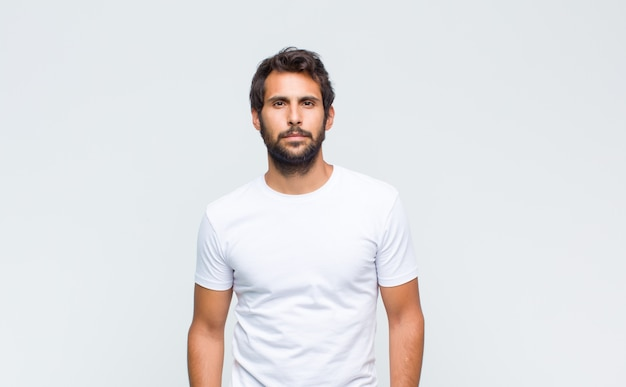 Молодой красивый латинский мужчина позирует и смотрит вперед против белой стены