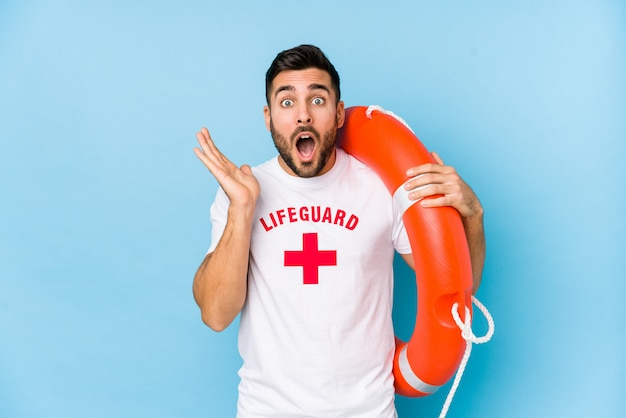 Young handsome lifeguard man isoalted surprised and shocked.