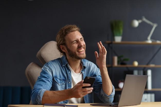 노트북으로 사무실에서 일하고 긍정적인 표현을 하는 젊고 잘생긴 장발 곱슬머리 남자. 행복한 사업가는 긍정적인 소식을 들었습니다. 보상, 새로운 계약, 좋은 거래, 성공적인 협상, 최고의 날.