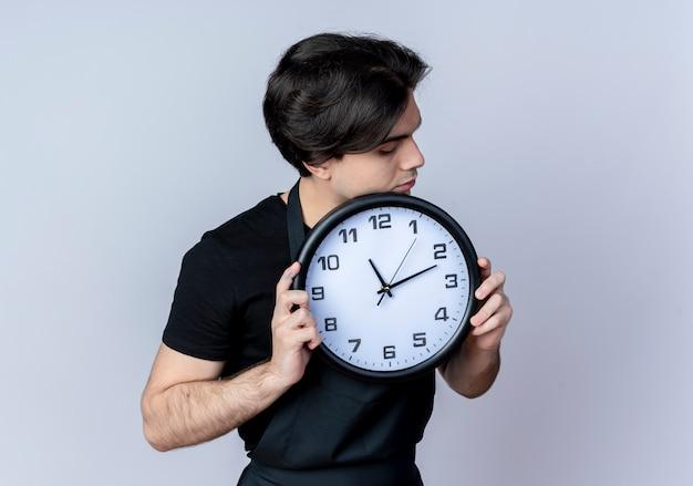 Giovane barbiere maschio bello in orologio da parete della holding uniforme intorno al fronte isolato su bianco
