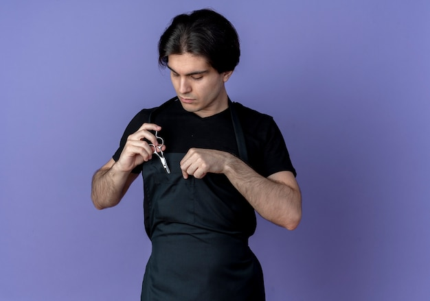 Giovane barbiere maschio bello in uniforme che mette le forbici in tasca isolata sull'azzurro
