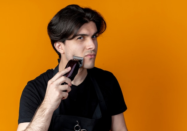 Young handsome male barber in uniform trimming his beard with hair clippers isolated on orange wall