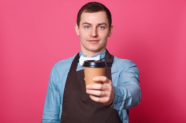 Young handsome male barista suggests you cup of coffee made by him, white bow tie and brown apron