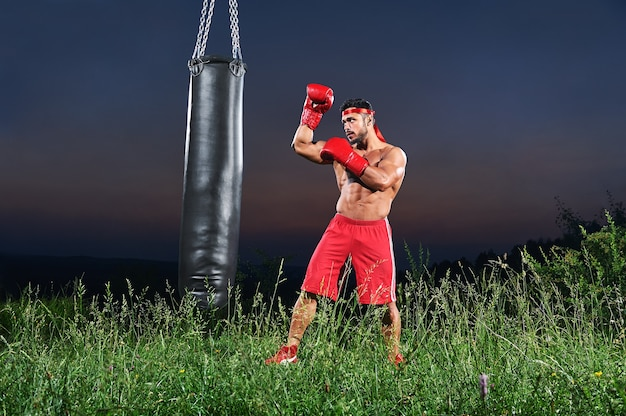 Young handsome male boxer practicing on a punching bag outdoors Free Photo