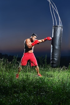 Young handsome male boxer practicing on a punching bag