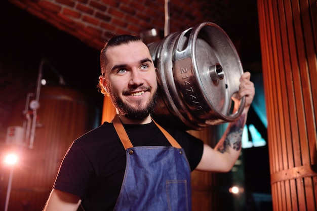 A young handsome male brewer holds an iron barrel with beer on the background of the brewery and beer tanks