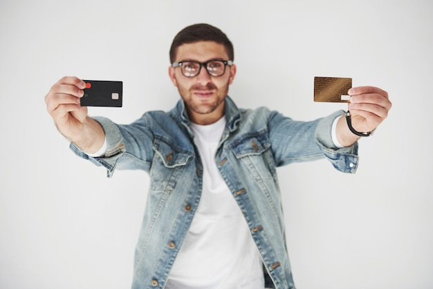 Young handsome male business executive in casual attire holding a credit card in the pockets on a white background. the concept of trading on the internet and the ease of electronic money.