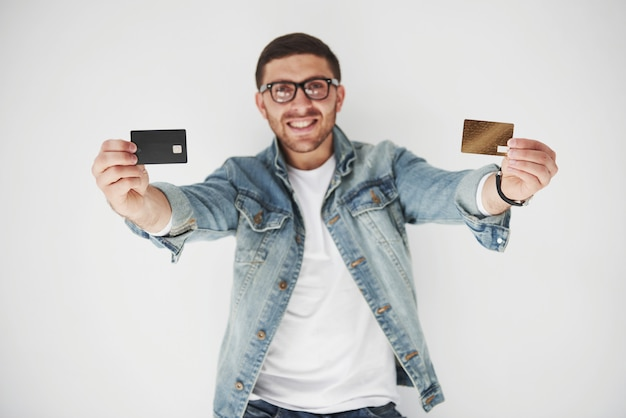 Young handsome male business executive in casual attire holding a credit card in the pockets on white