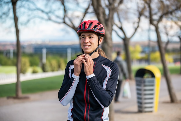 Young handsome male cyclist in sportswear buckling protective helmet in beautiful city park