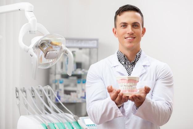 カメラに義歯型を保持笑みを浮かべて若いハンサムな男性歯科医