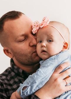 若いハンサムな男性の父親は、娘のインファンタを優しく抱きしめます