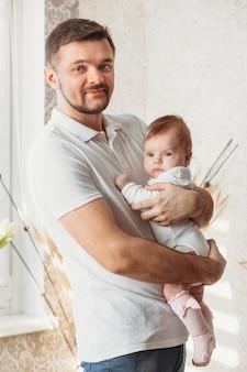 若いハンサムな男性の父は明るい部屋で女の赤ちゃんを保持します