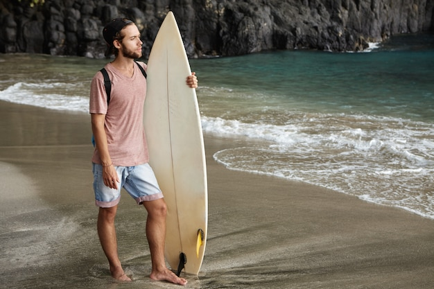 Young handsome male model posing with surfboard on exotic beach