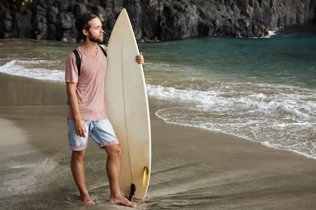 이국적인 해변에서 서핑 보드와 함께 포즈 젊은 잘 생긴 남성 모델