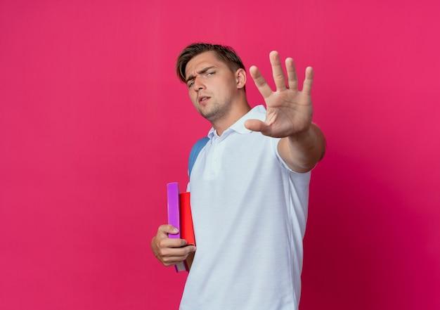 Giovane studente maschio bello che indossa la borsa posteriore tendendo la mano isolata sul muro rosa