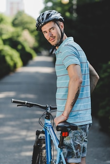 Young handsome male wearing helmet standing with bicycle on straight road