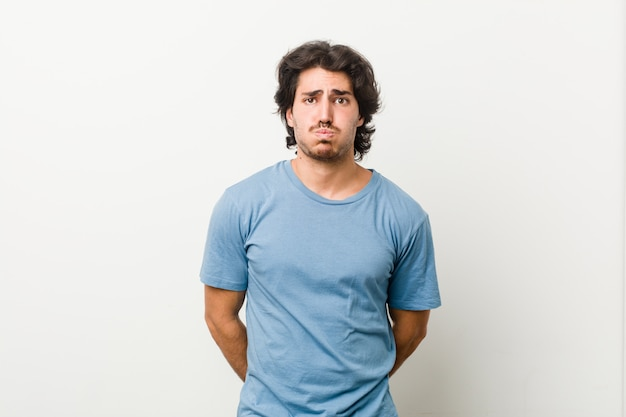 Молодой красавец на белой стене дует щеки, усталое выражение. концепция выражения лица.