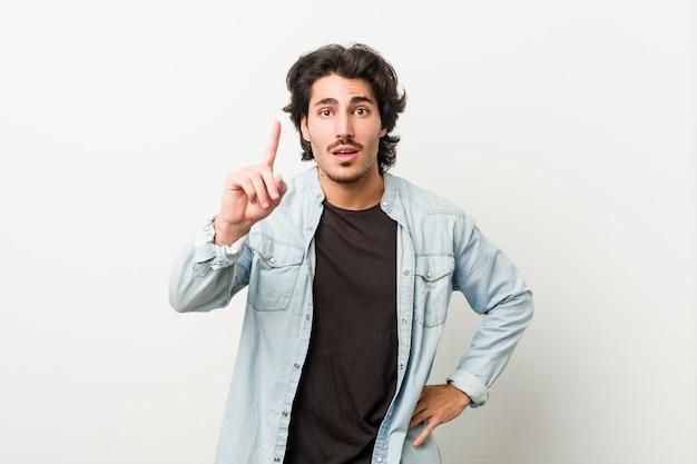 アイデア、インスピレーションの概念を持つ白い壁に若いハンサムな男。