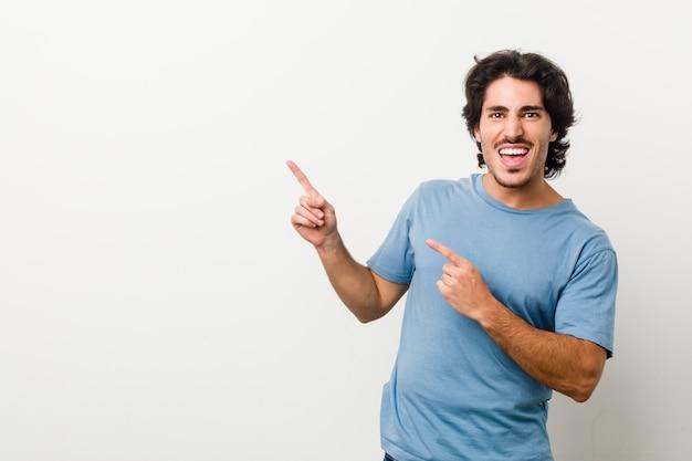 Молодой красавец против белой стене, указывая указательными пальцами на копией пространства, выражая волнение и желание.