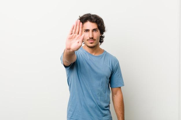 あなたを防ぐ差し出された手を示す差し出された手で白い壁に立っている若いハンサムな男。