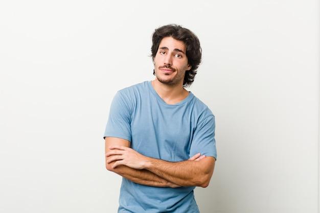 皮肉な表情でカメラで見て不幸な白い壁に若いハンサムな男。