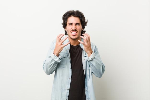 白い壁に対して若いハンサムな男は、緊張した手で叫んで怒っています。
